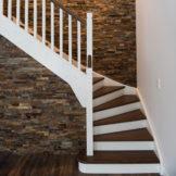 Tät L-trappa med steg i laserad ek, sidovang i vitmålat utförande och blocksteg. Räcke Classic i vitmålat utförande med överliggare i laserad ek.