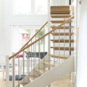 Öppen L-trappa. Steg i ek och sidovang i vitmålat utförande. Räcke Funk med handledare i ek och spjäla nr 11 i rostfritt stål.