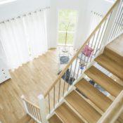 Öppen L-trappa. Steg i ek och sidovang i vitmålat utförande. Räcke Funk med överliggare i ek och spjäla nr 11 i rostfritt stål.