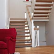 Öppen U-trappa med vilplan. Steg i ek och sidovang i vitmålat utförande. Räcke Classic med handledare i ek och spjälor i vitmålat utförande.