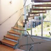 Trappa Profil med steg i oljad bambu och vang i rostfritt stål. Räcken av glas.