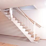 Öppen L-trappa. Steg i ek och underliggande vang i vitmålat utförande. Räcke Ballade med handledare i ek och spjäla nr 11 i rostfritt stål.