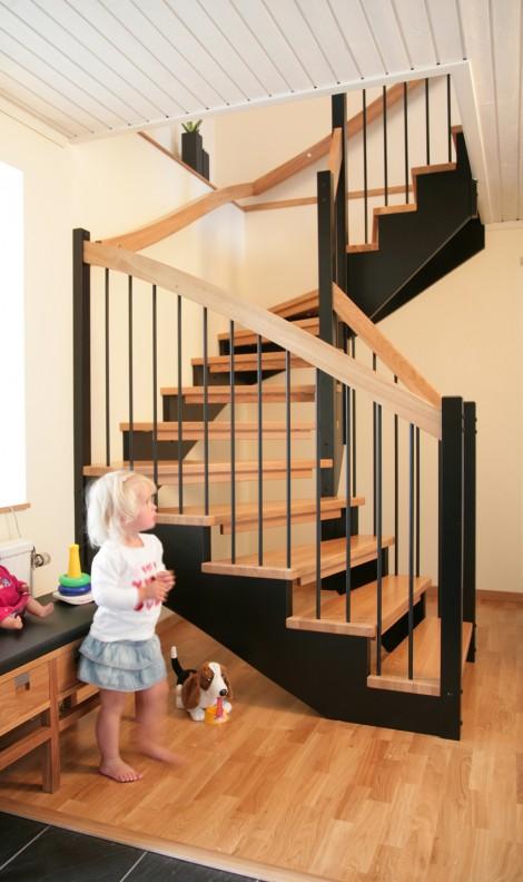 Öppen U-trappa med steg i ek och underliggande vang i svartmålat utförande. Räcke Pop med handledare i ek och spjäla nr 11 i svart.