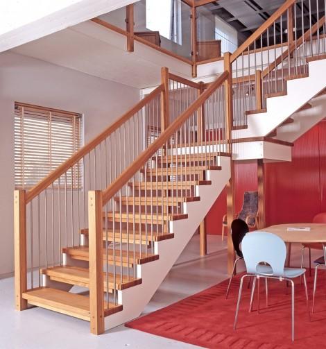 Öppen L-trappa med vilplan. Steg i ek och underliggande vang i vitmålat utförande. Räcke Pop i ek och spjäla nr 11 i rostfritt stål.