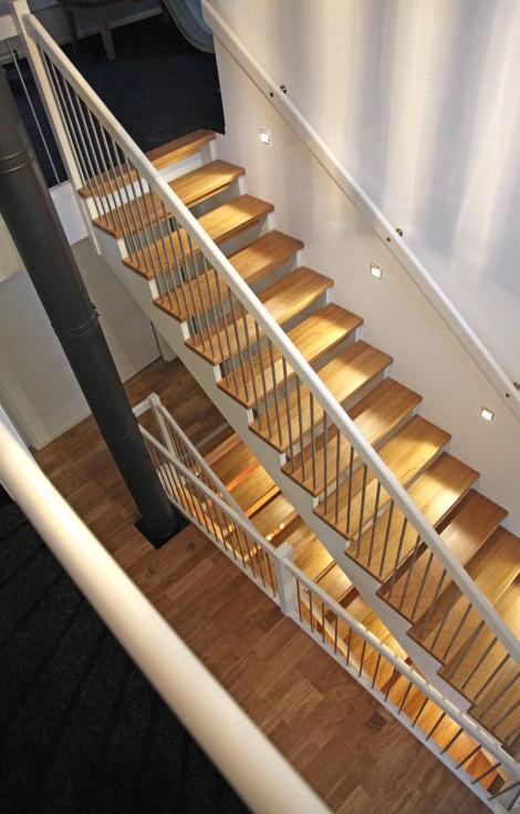 Öppen Rak-trappa med steg i ek och underliggande vang i vitmålat utförande. Räcke Pop i vitmålat utförande och spjäla nr 11 i rostfritt stål.