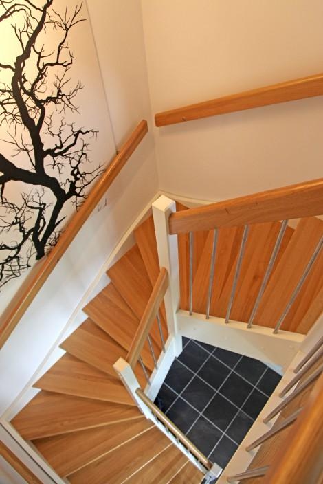 Tät U-trappa med steg i ek och sidovang i vitmålat utförande. Räcke Pop med handledare i ek och spjäla nr 11 i rostfritt stål.