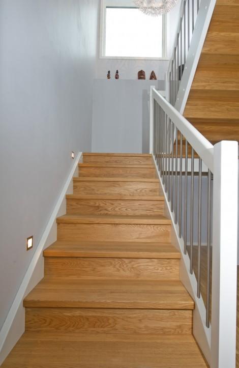 Tät U-trappa med vilplan. Steg i ek och sidovang i vitmålat utförande. Räcke Pop i vitmålat utförande och spjäla nr 11 i rostfritt stål.