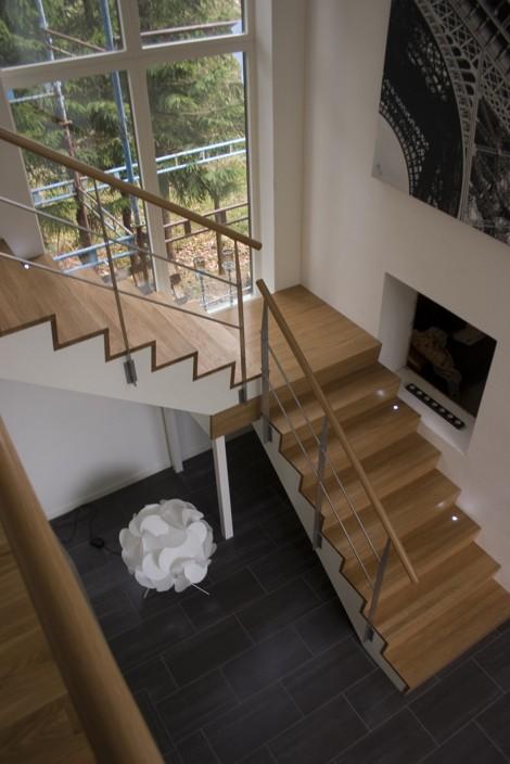 Trappa Zäta 2 med steg och sättsteg i klarlackad ek och vitmålad vang. Räcke 2 i rostfritt stål.