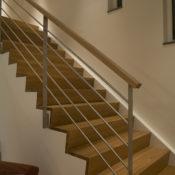 Trappa Zäta 2 med steg och sättsteg i klarlackad ek och vitmålad vang. Räcke 1 i rostfritt stål.